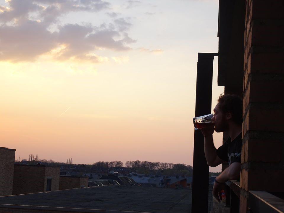 Un étudiant observe la ville depuis sa fenêtre en buvant un verre de bière.