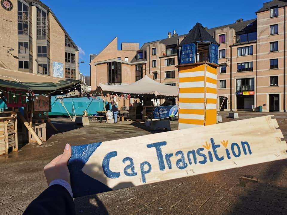 """pancarte """"Cap Transition"""" et installations festivalières en arrière-plan."""